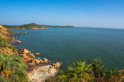 The scenery is beautiful rocky coast, blue sea and cloudless sky. Om beach, Gokarna, Karnataka, India. The scenery is beautiful rocky coast, blue sea and Royalty Free Stock Image