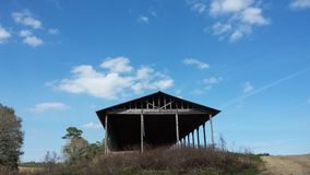Scenery. Blue skies over old tattered barn Royalty Free Stock Photography