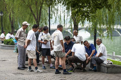 Scenery of Chinese park in Beijing. Some adult men play Chinese chess and others watching Stock Image