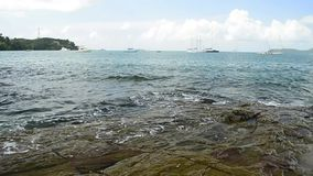 Scenery of coastline at Ao Yon beach, waves washed up on the rocks in low angle view, Andaman sea with yachts. Scenery of coastline at Ao Yon beach, waves stock video footage