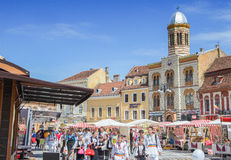 Scenery with folk costume children walking in council square(Piata Sfatului), landmark with Council House in medieval Brasov. Stock Images