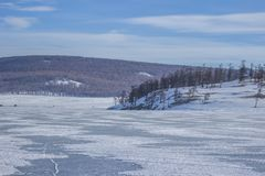 Scenery of frozen Lake Khovsgol in Mongolia with mountain range in Mongolia royalty free stock photo