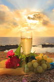 Scenery with glass of white wine. Glass of white wine, grapes and flowers on a background of sea and sky at sunset stock image