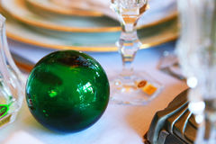 Scenery of the green ball and tableware of the table. Landscape of table with green sphere and dish and glass cup Stock Photography