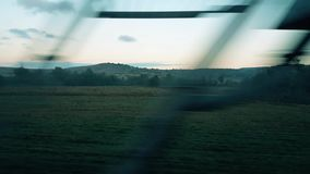 Rural scene through the passenger train window. Scenery of green fields with trees from the window of a passenger train stock footage