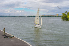 Scenery with lonely fisherman, sailboat and flying gull on a Dnepr river embankment. DNEPR, UKRAINE - SEPTEMBER 24, 2016:Scenery with lonely fisherman, sailboat stock images