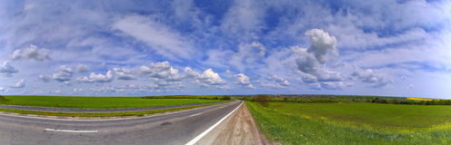 Scenery panorama. Road to the skyline; Blue sky with clouds and green grass on the roadside Royalty Free Stock Photos