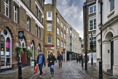 Scenery of people walking in the streets of Soho, London under the gloomy sky