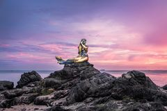 Scenery of a popular public statue of a golden mermaid on stone at Samila Beach in Songkhla Province at sunrise with island and sh. Ips in the background Royalty Free Stock Image