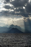 Scenery of sea and mountains on background of sky in sun rays Royalty Free Stock Images