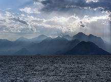 Scenery of sea and mountains on background of sky in sun rays Royalty Free Stock Photography