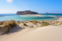 Scenery of sunny summer day with sand beach, turquoise sea and mountains. Place for tourists rest Balos lagoon, Crete island. Scenery of sunny summer day with royalty free stock photography