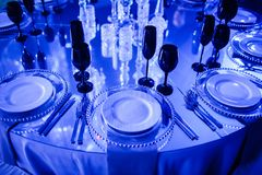 Scenery table with blue lights and black glasses royalty free stock images
