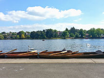 Scenery. Tethered boats and few swans on the lake in Roath Park, Cardiff, UK. Tourism attraction Royalty Free Stock Photo