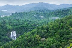 Scenery top view of beautiful waterfall in tropical forest, fres. H mist, wild flowers with green mountains in rainy day. Khlong Lan National Park, Thailand royalty free stock images