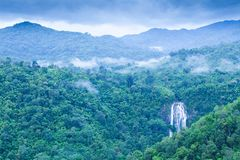 Scenery top view of beautiful waterfall in tropical forest, fresh mist, wild flowers with green mountains in rainy day. Khlong Lan. National Park, Thailand stock photography