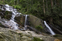 Scenery of tropical waterfall flowing through the beautiful green forest. Amazing scenery of tropical waterfall flowing through the beautiful green forest Stock Photo