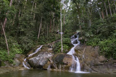 Scenery of tropical waterfall flowing through the beautiful green forest. Amazing scenery of tropical waterfall flowing through the beautiful green forest Royalty Free Stock Image