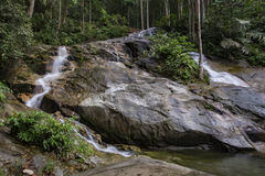 Scenery of tropical waterfall flowing through the beautiful green forest. Amazing scenery of tropical waterfall flowing through the beautiful green forest stock images