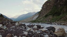 Scenery view of rocky stream in mountain covered in green trees, snowy peaks. Scenery view of fast rocky stream in mountain covered in green trees, snowy peaks stock video