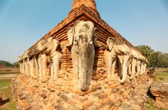 Scenery of Wat Sorasak, an ancient Buddhist Temple with elephant sculptures supporting the base of the stupa royalty free stock photography