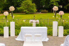 Scenery of the wedding ceremony in the park. White frame decorated with flowers. Ceremony in white style Stock Image