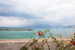 Scenic Aegean seascape with flowers and lighthouse Royalty Free Stock Photos