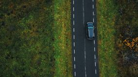Scenic aerial top view close-up, drone tracking black SUV car moving along highway road along cloudy autumn forest. Cinematic opening scene, modern vehicle on stock footage