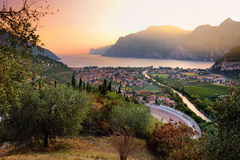 Scenic aerial view of Riva del Garda town, located on a shore of Garda lake, surronded by beautiful rocky mountains. Spectacular autumn sunset stock photos