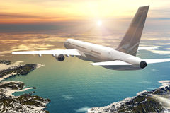 Scenic airliner flight in sunset. Scenic airliner flight over the ocean and mountains in sunset Royalty Free Stock Image