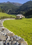 Scenic alpine meadow, hut an mountains Stock Image