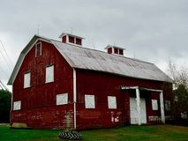 Classic Red Barn With White Boarded Up Windows. Scenic Americana classic red barn with white boarded up windows and door, Pennsylvania countryside royalty free stock image