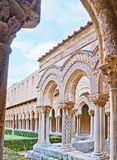 The scenic arcade in Monreale Cloister's garden. The old garden of Monreale Cloister surrounded by the scenic arcade with unique columns, decorated in different Royalty Free Stock Photos