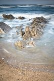 Scenic atlantic coastline with waves in motion around rocks on sandy beach in long exposure, bidart, basque country, france. Scenic atlantic coastline with waves Royalty Free Stock Photo