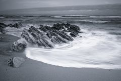 Scenic atlantic coastline with waves in motion around rocks on sandy beach in long exposure, bidart, basque country, france Stock Photos