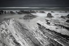 Scenic atlantic coastline with waves in motion around rocks on sandy beach in long exposure, bidart, basque country, france Royalty Free Stock Photo