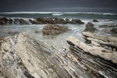 Scenic atlantic coastline with waves in motion around rocks on sandy beach in long exposure, bidart, basque country, france. Scenic atlantic coastline with waves Stock Photography