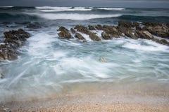 Scenic atlantic coastline with waves in motion around rocks on sandy beach in long exposure, bidart, basque country, france. Scenic atlantic coastline with waves Stock Photo