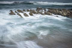 Scenic atlantic coastline with waves in motion around rocks on sandy beach in long exposure, bidart, basque country, france. Scenic atlantic coastline with waves Royalty Free Stock Image