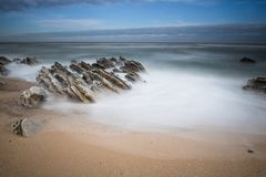 Scenic atlantic coastline with waves in motion around rocks on sandy beach in long exposure, bidart, basque country, france. Scenic atlantic coastline with waves Royalty Free Stock Photography