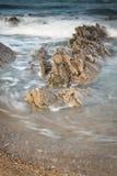 Scenic atlantic coastline with waves in motion around rocks on sandy beach in long exposure, bidart, basque country, france. Scenic atlantic coastline with waves Stock Image