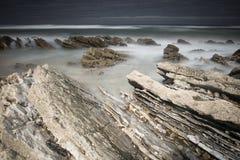 Scenic atlantic coastline with waves in motion around rocks on sandy beach in long exposure, bidart, basque country, france. Scenic atlantic coastline with waves Stock Photos