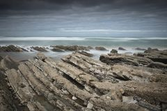 Scenic atlantic coastline with waves in motion around rocks on sandy beach in long exposure, bidart, basque country, france Stock Photography