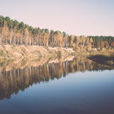 Scenic autumn colored river in country. Vintage. Royalty Free Stock Photo