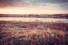 Scenic autumn landscape during dawn at river bank in rural field Royalty Free Stock Photo