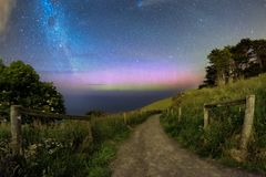 Scenic background of aurora and milky way galaxy. Beautiful southern lights caught together with Milky Way galaxy in Dunedin, New Zealand. There is a small royalty free stock photos