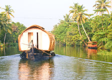 Scenic backwaters with house boats. Scenic and serene backwaters ,with house boats sailing on it, and greenery along the banks, in South India Stock Photos