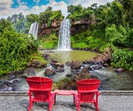 Scenic basaltic rock. Form famous waterfalls Iguazu Falls. Two large red plastic chairs - chaise lounges set at waterfalls. The concept of ecological tourism Stock Photography