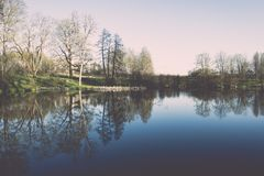 Scenic reflections of trees and clouds in water - retro vintage Stock Photography
