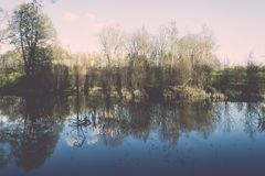 Scenic reflections of trees and clouds in water - retro vintage Royalty Free Stock Image